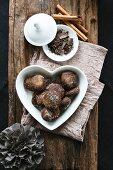 Chocolate and cinnamon treats in a heart-shaped bowl, grated chocolate, cinnamon sticks