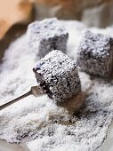 Lamingtons being coated in grated coconut