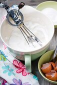 Whisked egg whites in a mixing bowl with a rotary hand whisk