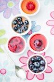 Several mini fruit jellies in eggcups