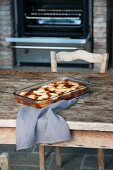 Pear clafoutis in the baking dish on a wooden table in front of the oven