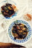 Two plates of Provençal mussels served with white bread