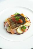 Fried sea bass fillet on a bed of vegetables