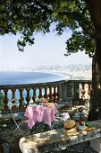 A table laid for a meal with salad niçoise on a balcony with a view over the city of Nice