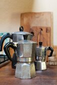 Three espresso pots on wooden table