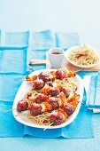 Meatball skewers with vegetables on spaghetti