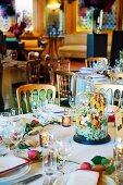 A celebration table with a floral arrangement under a glass cloche