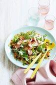 Quinoa salad with salmon, lettuce leaves, carrots and raisins