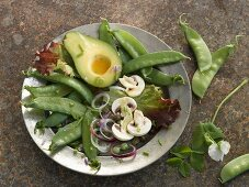 A plate of raw vegetables with sugar snap peas, avocado and mushrooms