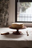 Golden Layer Cake with Pink Frosting on a Wooden Cake Plate