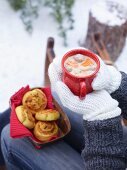 Hands holding an enamel mug of bean and potato soup with meat dumplings with a basket of pumpkin and leek whirls
