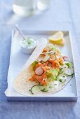 Wrap filled with smoked salmon, cucumber and radishes