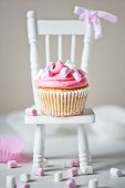 Single marshmallow cupcake with pink and white marshmallows on white dolls house chair with pink ribon