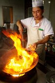 A Chinese chef with a wok of burning oil