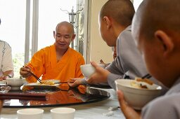 Monks eating in a Chinese monetary