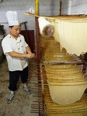A Chinese chef standing next to drying tofu skins