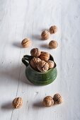 Walnuts in a ceramic jug and to one side