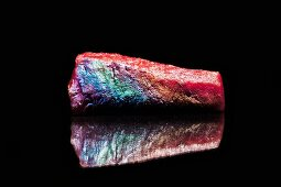 A raw piece of salmon coated in colors of eye shadow creating a rainbow effect