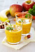 A smoothie made from bananas, carrots, apples, nuts and raisins