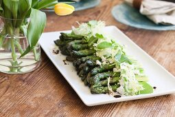 A Platter of Asparagus topped with Grated Cheese, Greens and Balsamic Vinegar