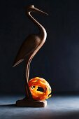 A wooden bird with a nest of tomato tagliatelle