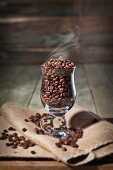 A Glass Coffee Cup with Steaming Coffee Beans on a folded Burlap Bag