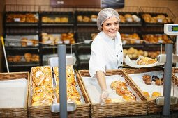 Young sales assistant holding sweet pastries