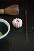 A wagashi chrysanthemum (kiku), a tea whisk, a matcha spoon and matcha tea