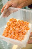A hand holding a plastic container of sea buckthorn confectionery