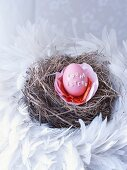 Dyed egg decorated with alphabet noodles in nest of hay and feathers