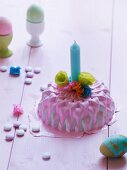 Miniature cake decorated with pink icing, candle & paper flowers