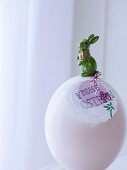 White ostrich egg decorated for Easter with rabbit ornament & pendant