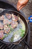 Lamb chops in a pan over a camp fire