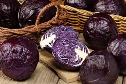 Red cabbage in baskets and on a chopping board, whole and cut in half
