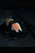 Nigiri sushi with crab between sheets of salty nori (Japan)