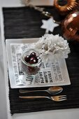 A Christmassy place setting with floral decoration and Christmas tree baubles