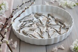 Forks and name tags in a baking dish surrounded by catkins, hyacinths and garlic flowers