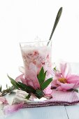 A glass of strawberry milk and peonies