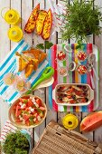Summer picnic with stuffed peppers, spinach omelette, muesli, fish, lemonade and watermelon salad