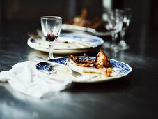 The remains of roast chicken with lemons, onions and thyme, on plates
