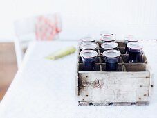 Several bottles of home-made elderberry juice in a wooden crate