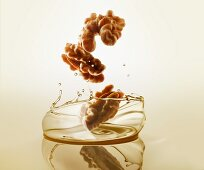 Walnuts falling into walnut oil