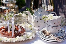 Chocolate cake, white lilac flowers and a teaset on a table in the garden