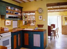 A petrol blue kitchen in an English country house, with a view into the adjacent dining room