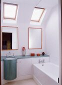 A bright bathroom with a bathtub, wall mirrors above the basins, and decorative objets d'art