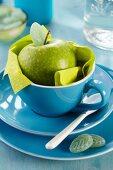 Grüner Apfel mit blattförmigem Bonbon in blauer Tasse