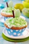 Apfelmuffins mit Zuckerguss, grünen Zuckerstreuseln, Schokostick und blattförmigem Bonbon - als Apfel verziert