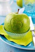 Grüner Apfel in Muffinförmchen auf Teller mit eingeritztem Herz