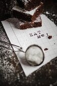 Three brownies stacked one on top of the other on a white scrap of paper with the writing Eat Me