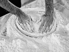 Hands pressing pizza dough flat